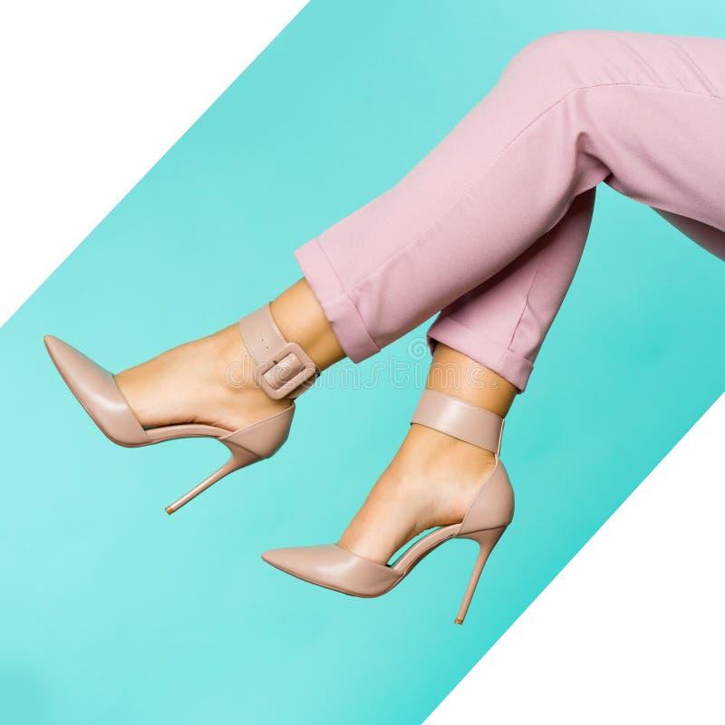 Sexiga ben i bruna skor för höga häl på blå bakgrund arkivbild
