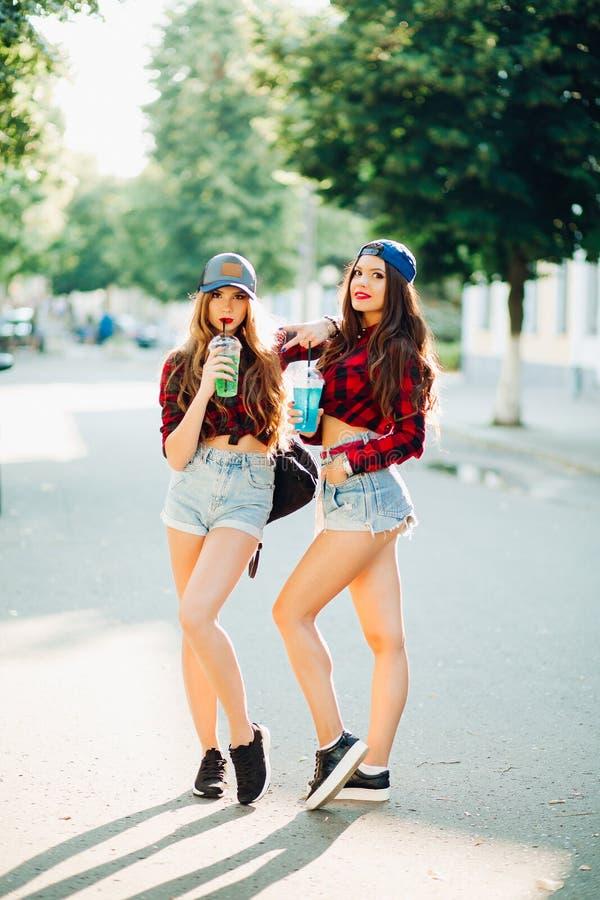 Sexiga hipsterflickor som poserar på gatan och dricker fruktsaft royaltyfri bild