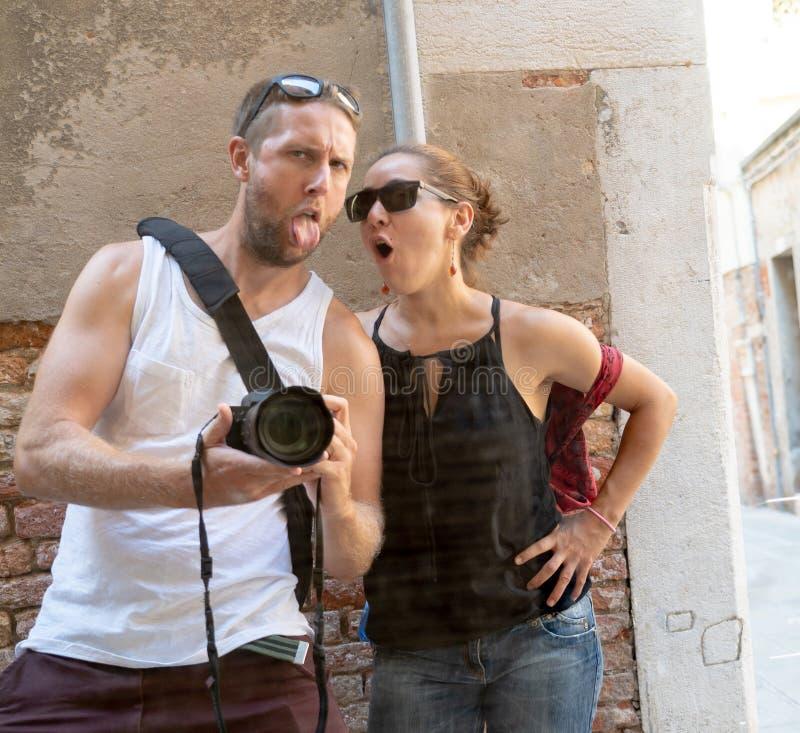 Sexiga kalla par som har gyckel som tar en selfie på fönsterreflexionsanseende vid tegelstenväggen arkivbilder