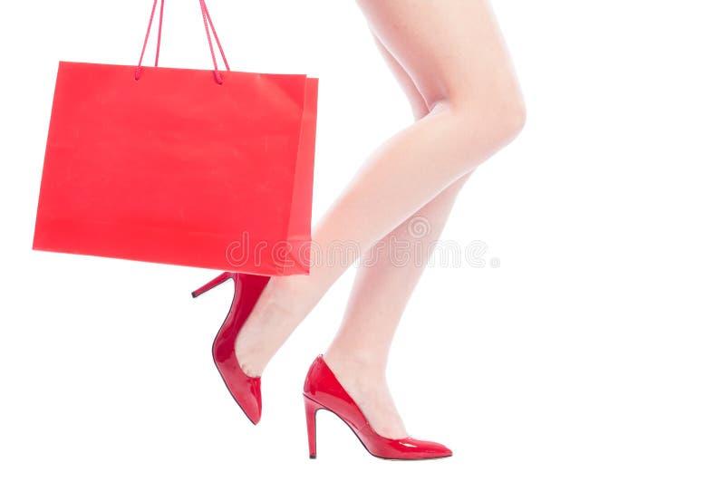 Sexiga kvinnaben, röda skor och shoppingpåse arkivbild
