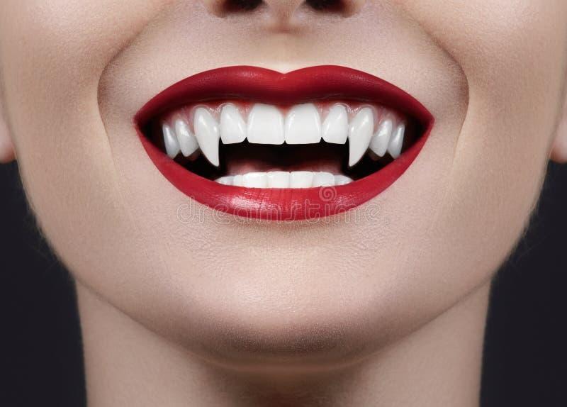 Sexiga kvinnliga vampyrkanter Gigantiskt leende Allhelgonaaftonstil med den röda blodmakeupkanten Maskeradblick med ruskiga fags royaltyfri bild