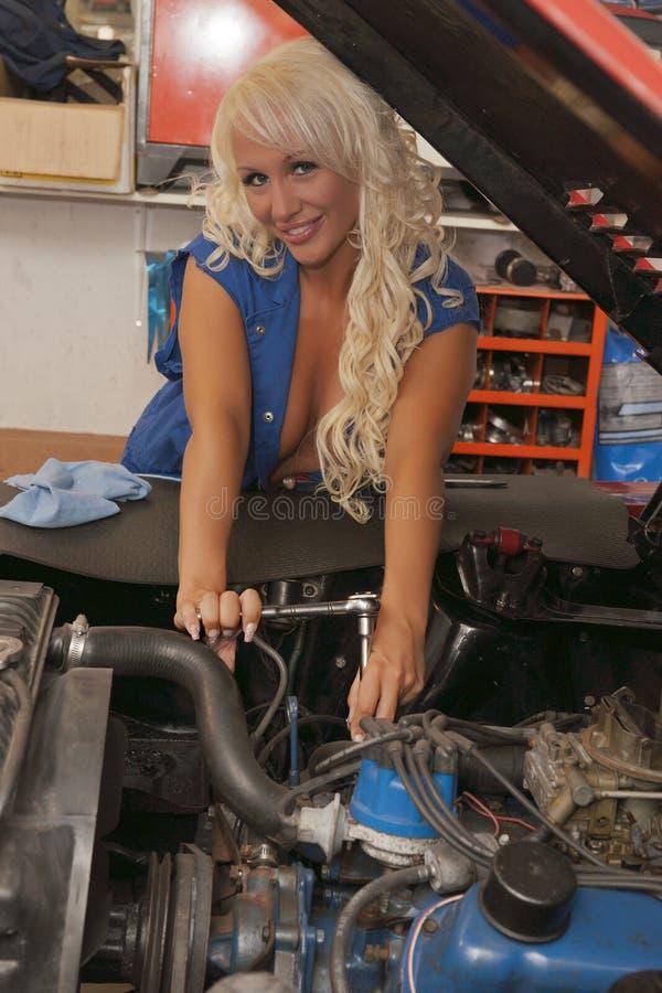 Sexiga kvinnor reparerar bilen royaltyfria bilder