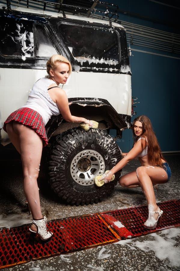 Sexiga kvinnor som tvättar bilen arkivfoton