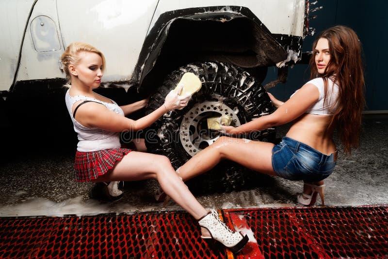 Sexiga kvinnor som tvättar bilen royaltyfria foton