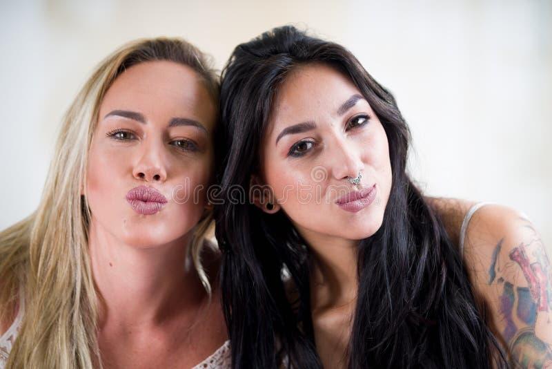 Sexiga lesbisk kvinnavänner på morgon-, blondin- och brunettflickor, i en vit bakgrund royaltyfri bild