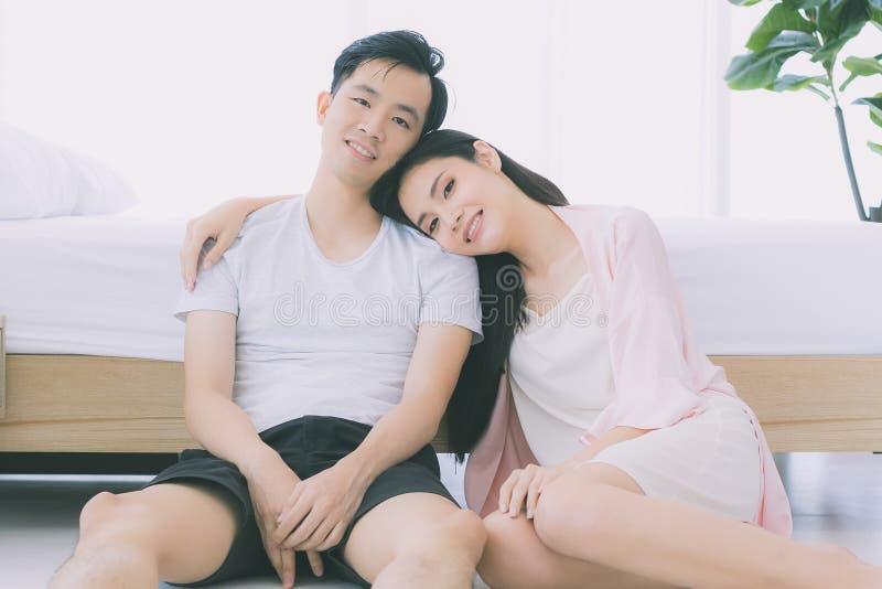 Sexiga par i pyjamas sitter p? golv i sovrum fotografering för bildbyråer