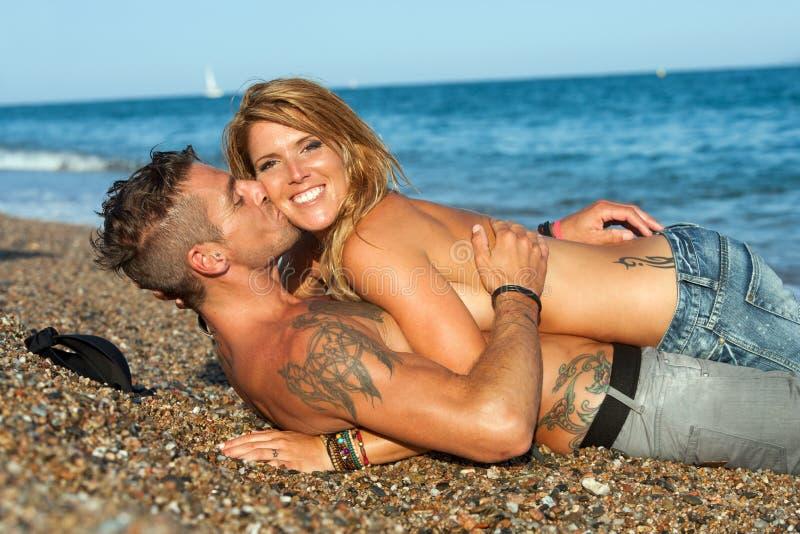 Sexiga par som lägger på Pebble Beach. arkivfoton