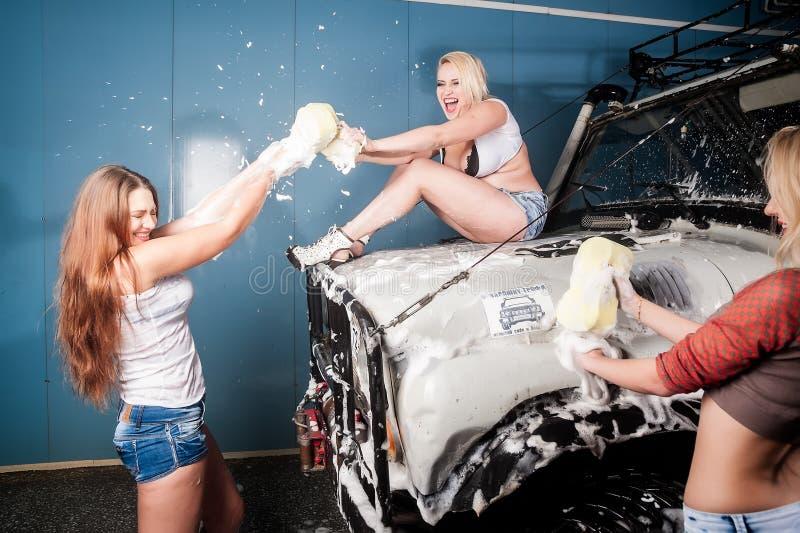 Sexiga skämtsamma kvinnor som tvättar bilen med gyckel royaltyfri fotografi