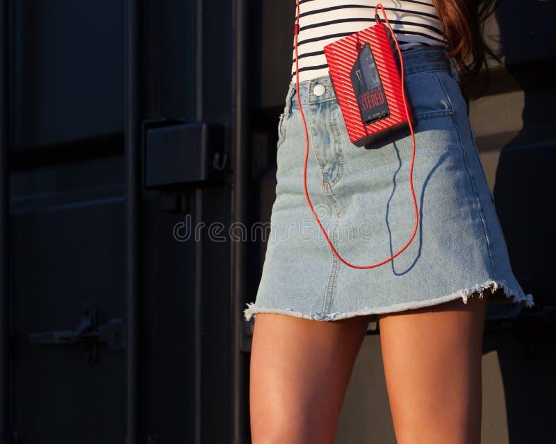 Sexigt av den nätta unga sportstilkvinnan som poserar på semester på gatan som har gyckel med den röda kassettspelaren för tappni royaltyfri fotografi