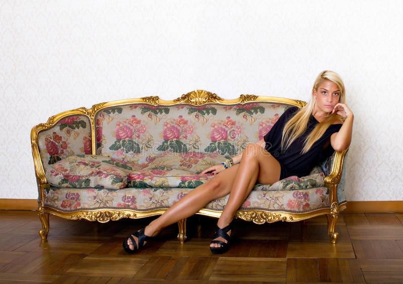 Sexigt blont uttrycka på sofaen arkivbilder