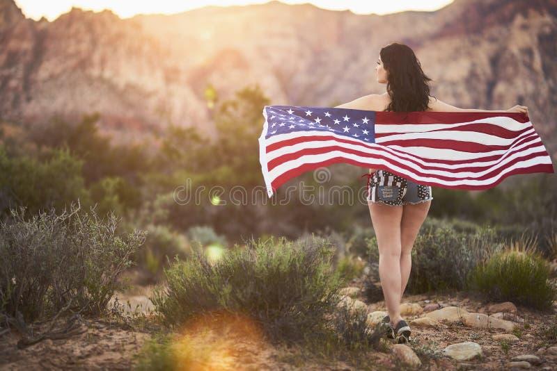 Sexigt flickaanseende med amerikanska flaggan i den nevada öknen på solnedgången royaltyfri bild