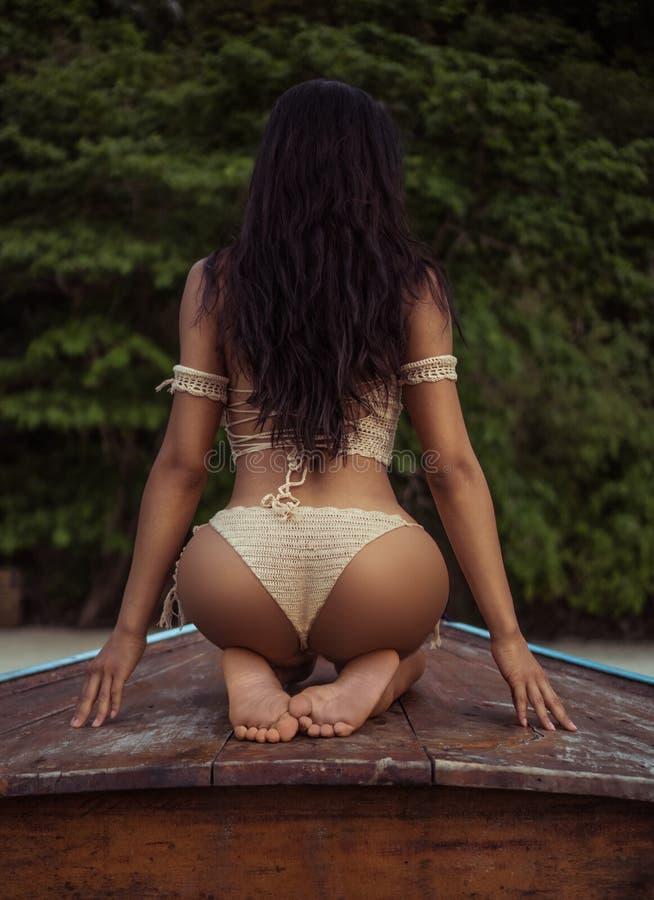 Sexigt flickasammanträde på en pilbåge - tillbaka sikt royaltyfria foton
