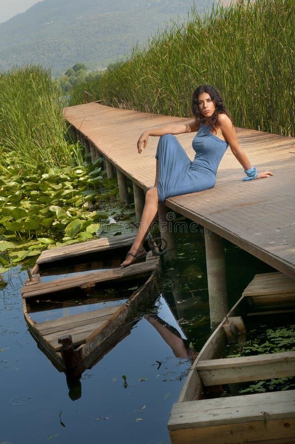 Sexigt flickasammanträde på en pir royaltyfri fotografi