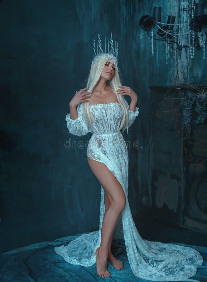Sexigt gotiskt, snödrottning i en vit tappningklänning som poserar med ett kalt ben En blond flicka i en krona med istappar på a royaltyfria bilder