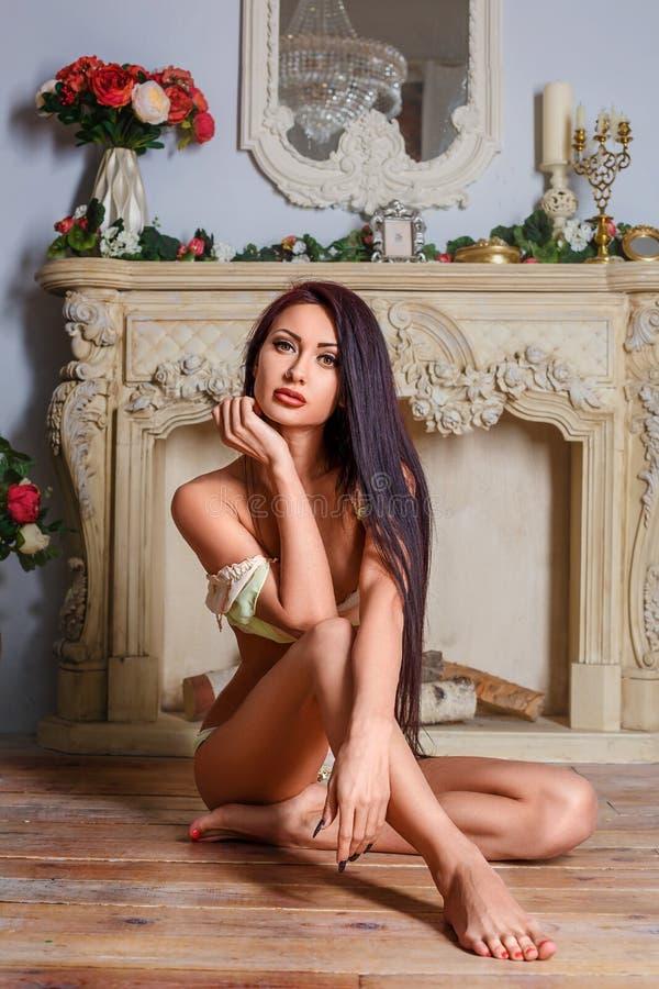 Sexigt kvinnasammanträde för härlig brunett i hennes underkläder på golvet royaltyfri fotografi