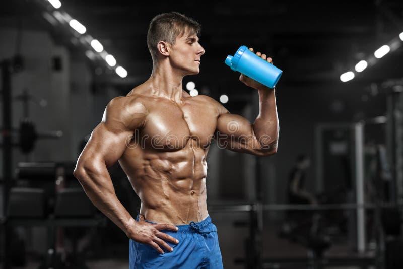 Sexigt muskulöst mandricksvatten i idrottshallen, format buk- Stark manlig naken torsoabs som utarbetar arkivbilder