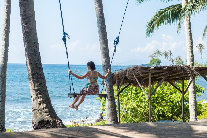 Sexigt sammanträde för ung kvinna på gungan på den tropiska stranden, paradisö Bali, Indonesien Solig dag lycklig semester arkivbild