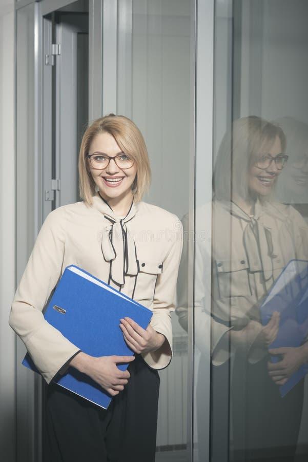 Sexigt sekreterareleende med dokument Affärskvinna med affärslegitimationshandlingar Lycklig kvinnahållmappmapp i regeringsställn royaltyfri fotografi