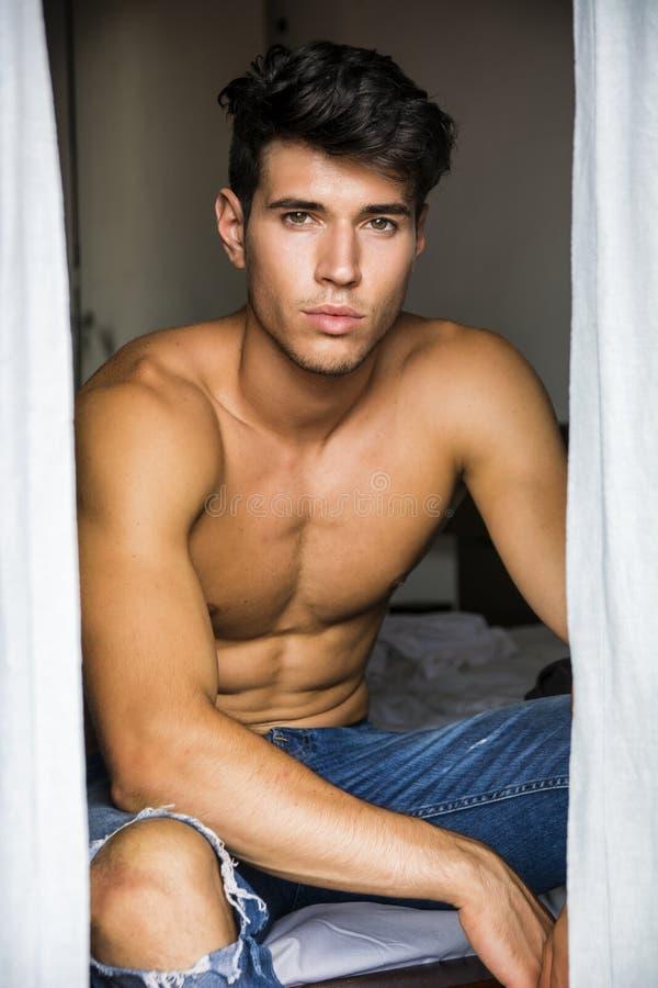 Sexigt sitta för ung man som är shirtless vid gardiner arkivfoton