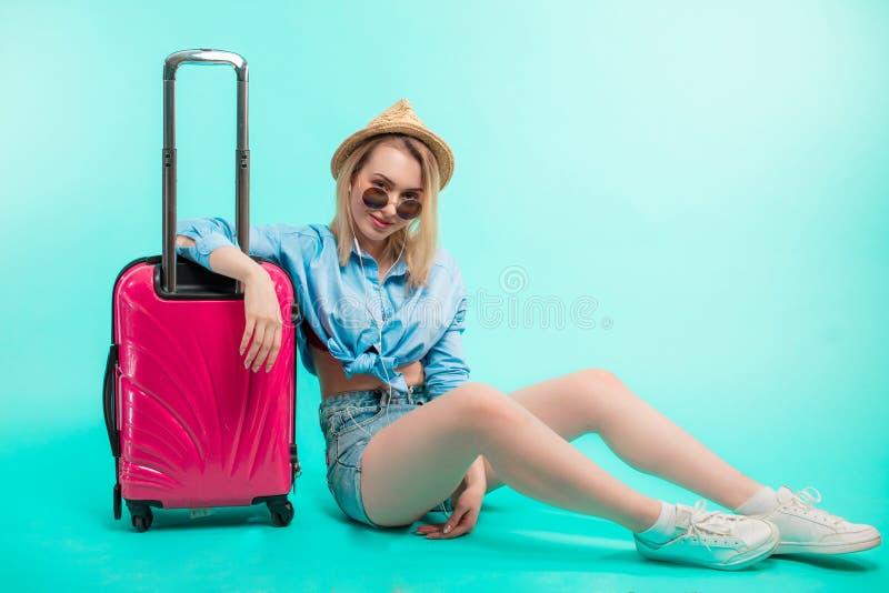 Sexigt stilfullt handelsresandesammanträde på golvet med rosa bagage arkivfoto