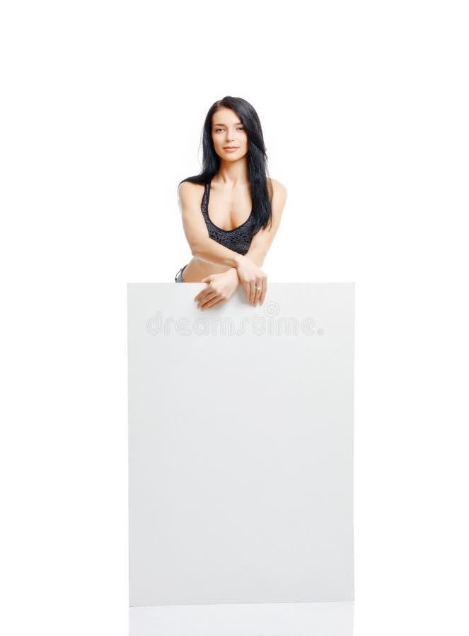 Sexigt ung flickaanseende och innehav en vit platta som isoleras på w arkivbild