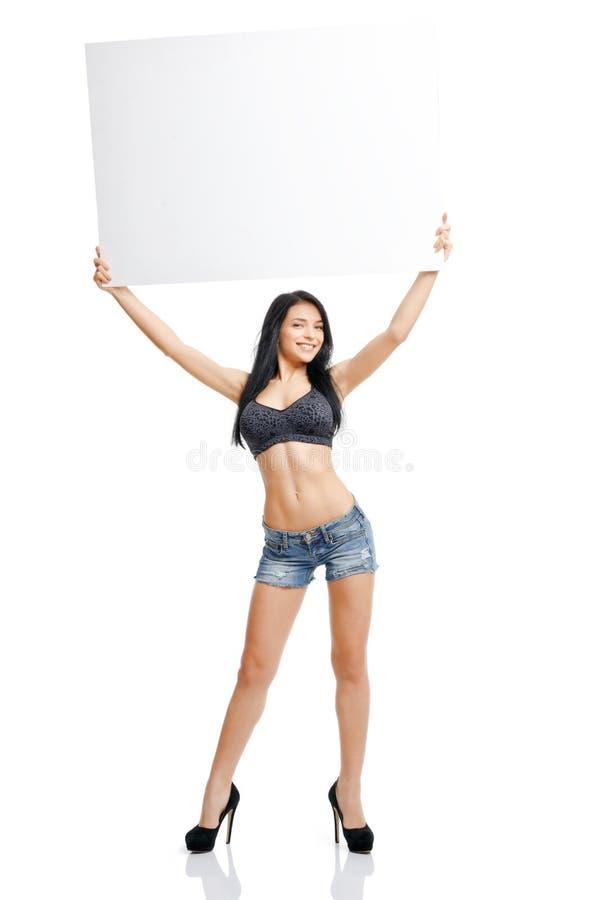 Sexigt ung flickaanseende och innehav en vit platta som isoleras på w royaltyfria bilder