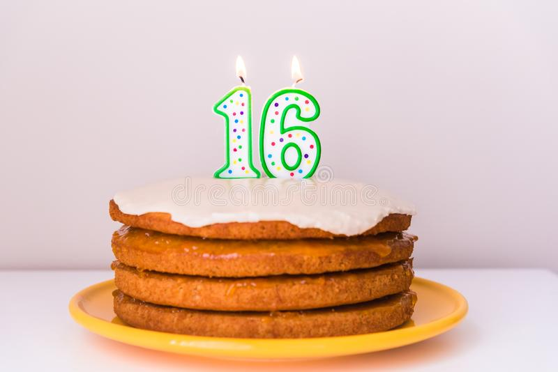 Sextonde födelsedagstearinljus på lantlig i lager strikt vegetarianvanilj bakar ihop royaltyfri bild