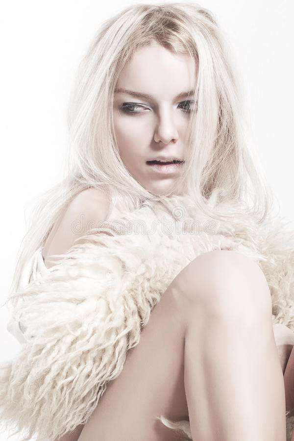 Sexual blonde posing in furs stock photography
