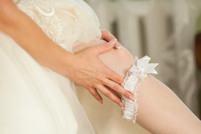 Sexual bride putting on wedding garter. Bride`s hands royalty free stock photos