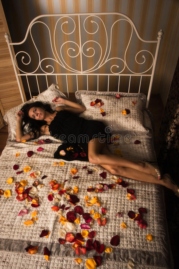 Sexual brunette lying on a bed royalty free stock photo