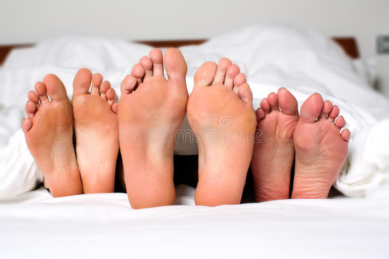 Sexual fantasies. Humorous image of the bare feet of a men and two women in bed sticking out from under the bedclothes conceptual of a threesome, orgy, swingers