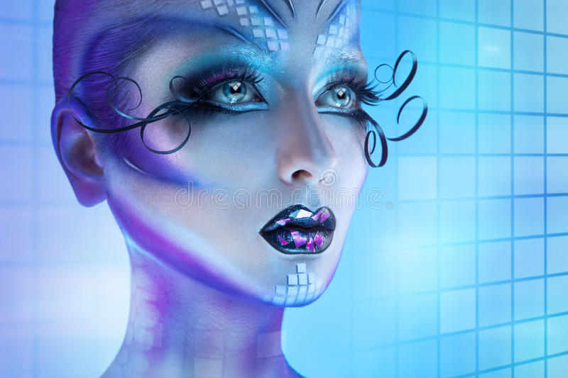 Sexual woman with creative body art. Looking away with blue eyes. Studio shot on blue background stock photo