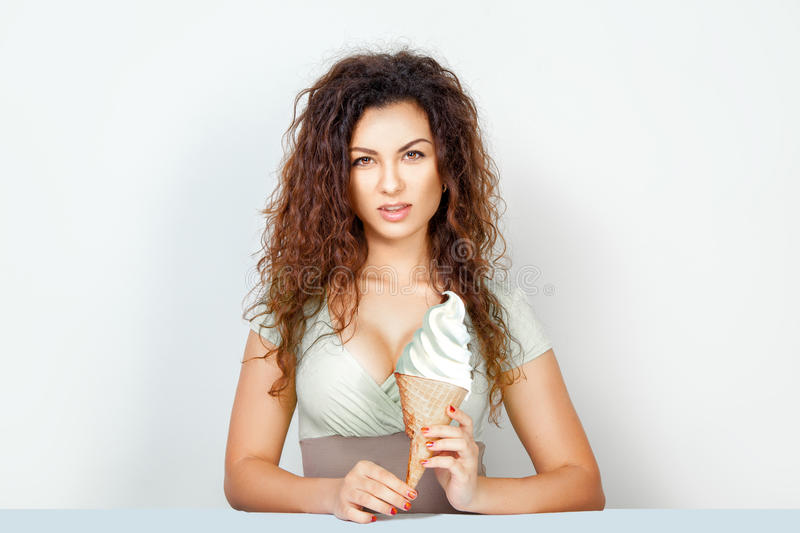 Sexual young woman with big ice cream once in hands. Sexual young woman with curly hair and brown eyes looking at the camera with big ice cream cone in hands stock photos