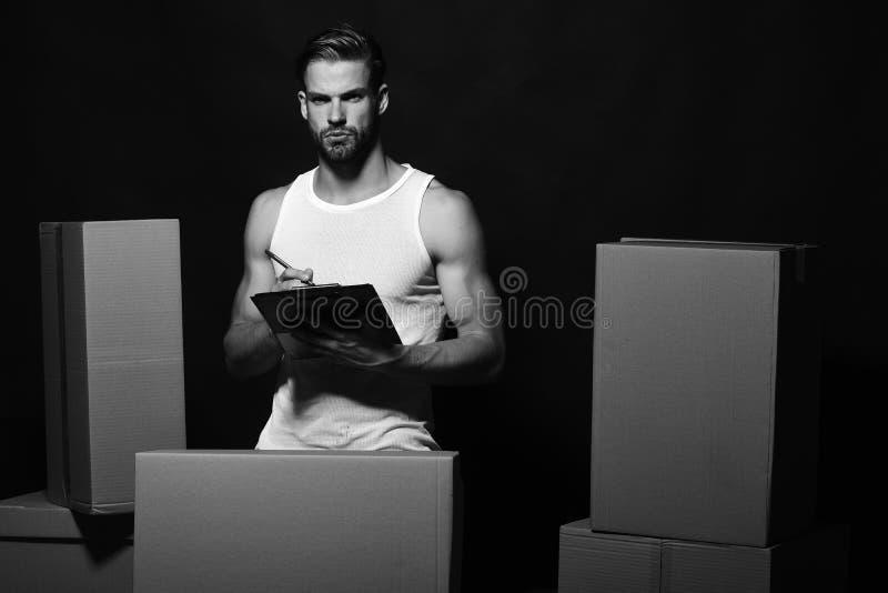 Sexualidad y concepto móvil El individuo con las manos musculares se coloca entre las cajas imágenes de archivo libres de regalías