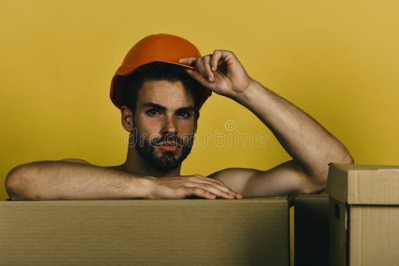 Sexualität und bewegliches Konzept Mann mit dem Bart lokalisiert auf gelbem Hintergrund Macho mit sexy Gesicht berührt Sturzhelm  lizenzfreies stockfoto