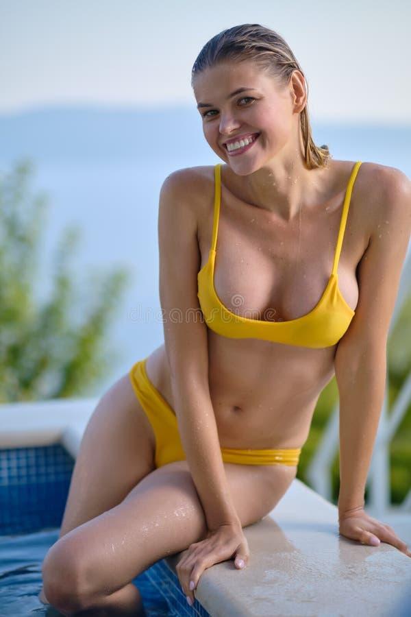 Sexualkvinna i bikini på solgarvat smal och formad kropp ligger nära simbassängen. arkivfoto