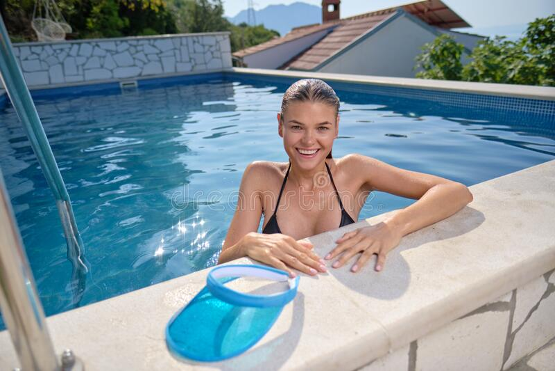 Sexualkvinna i bikini på solgarvat smal och formad kropp ligger nära simbassängen. arkivbilder