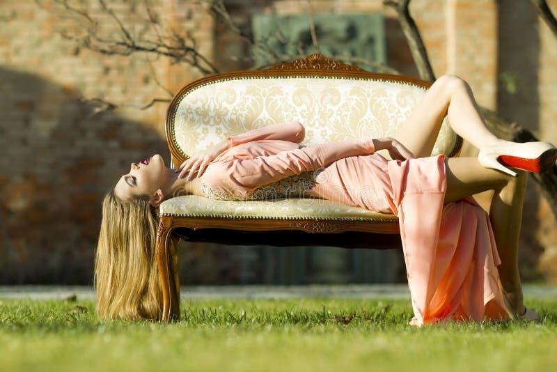Sexuell flicka på den utomhus- soffan royaltyfri bild
