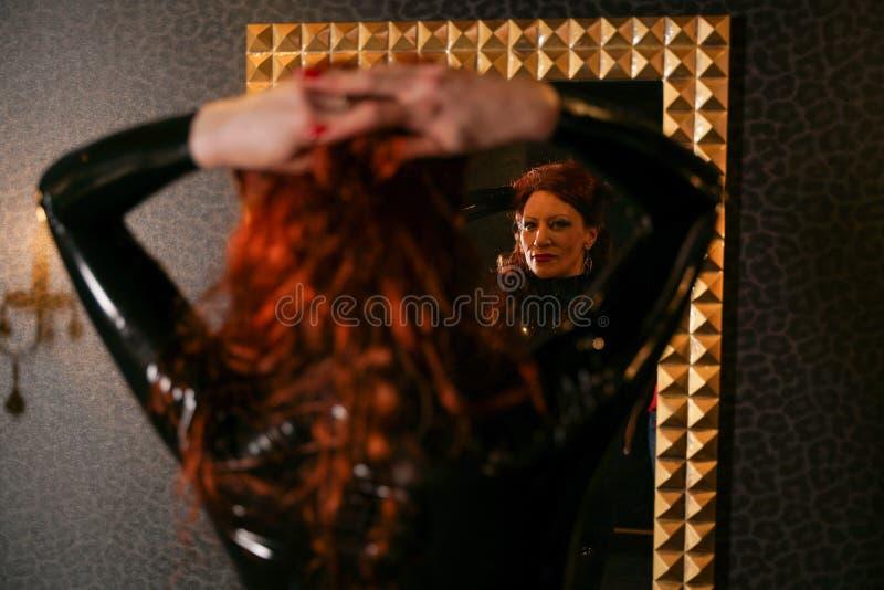Sexuelle Fetischrothaarigefrau, die schwarzes Latex catsuit trägt und den Spiegel in der Dunkelkammer betrachtet stockfotografie