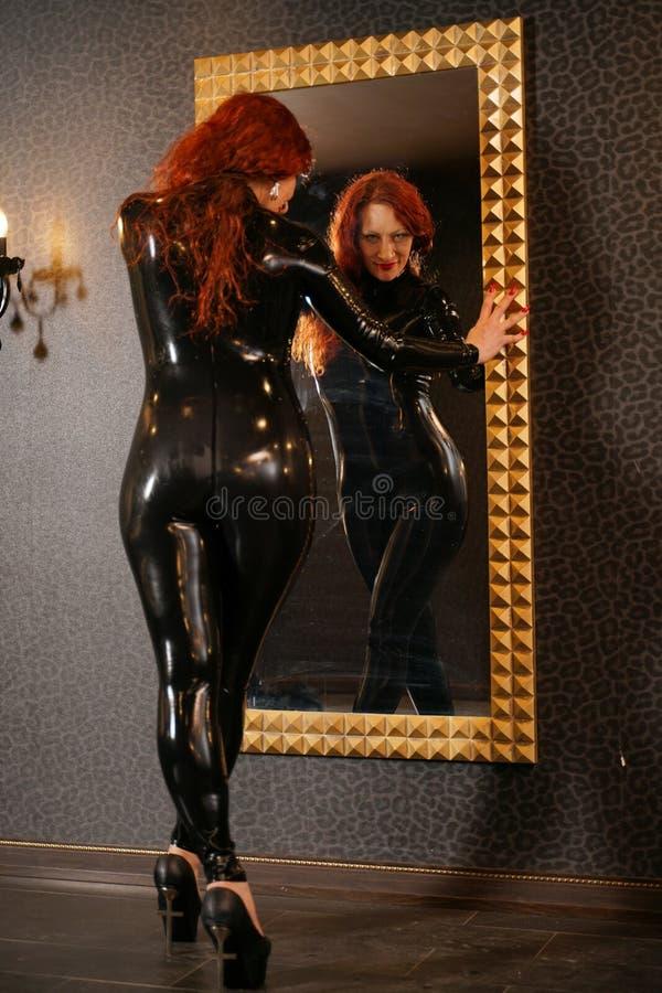 Sexuelle Fetischrothaarigefrau, die schwarzes Latex catsuit trägt und den Spiegel in der Dunkelkammer betrachtet stockbilder
