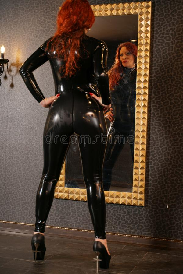 Sexuelle Fetischrothaarigefrau, die schwarzes Latex catsuit trägt und den Spiegel in der Dunkelkammer betrachtet lizenzfreies stockfoto