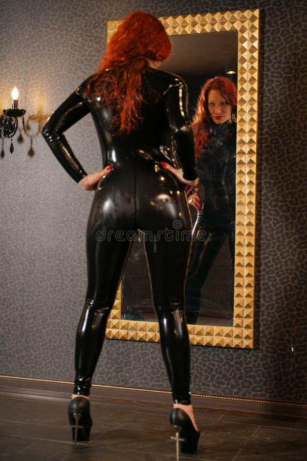 Sexuelle Fetischrothaarigefrau, die schwarzes Latex catsuit trägt und den Spiegel in der Dunkelkammer betrachtet lizenzfreie stockfotografie