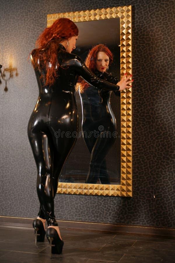 Sexuelle Fetischrothaarigefrau, die schwarzes Latex catsuit trägt und den Spiegel in der Dunkelkammer betrachtet lizenzfreie stockfotos