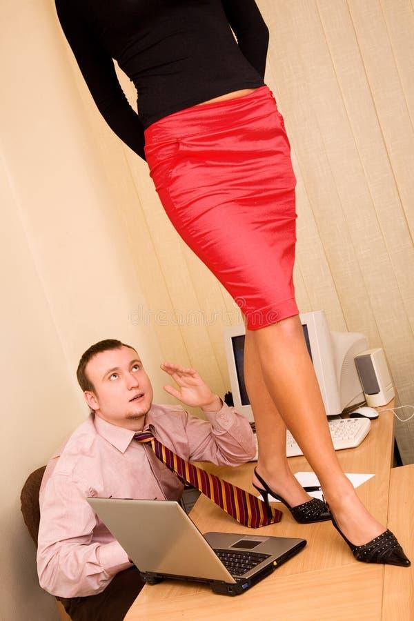 Sexuelle Frau, die auf Schreibtisch im Büro steht lizenzfreie stockfotos