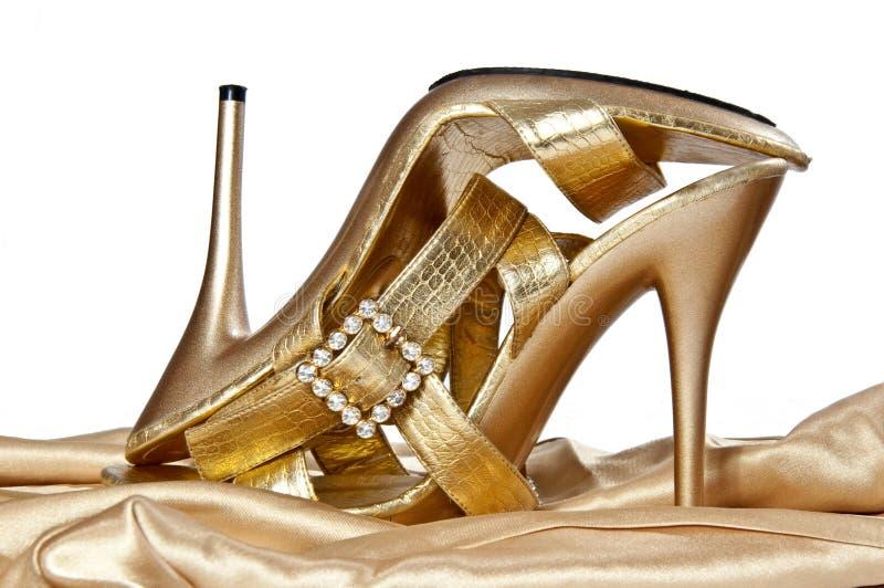 Sexuelle Goldschuhe auf einem hohen Absatz stockfotografie