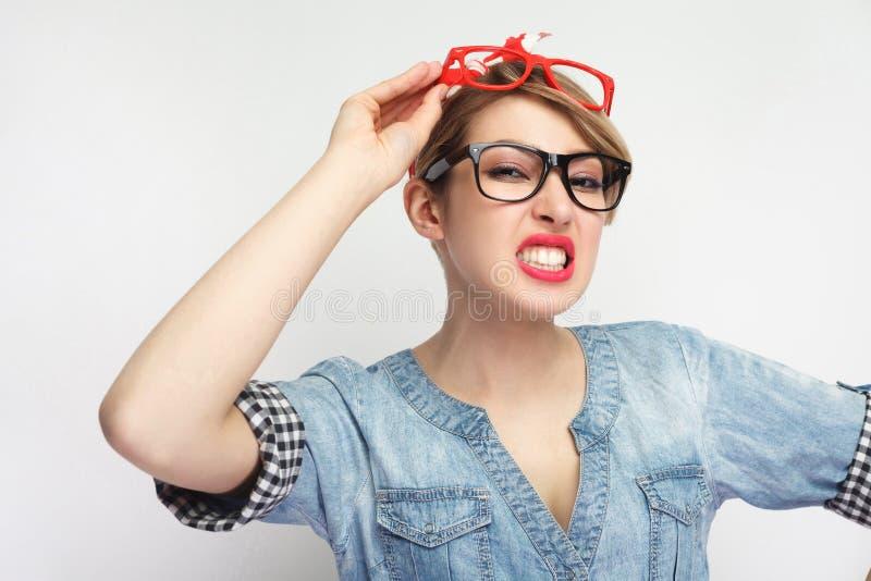 Sexuelle junge Frau des Ärgers im zufälligen blauen Denimhemd mit Make-upstellung, tragende viele bunte Schauspiele gleichzeitig, lizenzfreie stockbilder