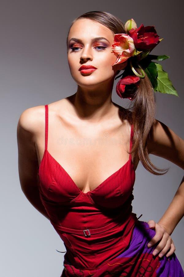 Sexuelles Mädchen im roten Kleid mit Blumen in ihrem Haar lizenzfreies stockfoto