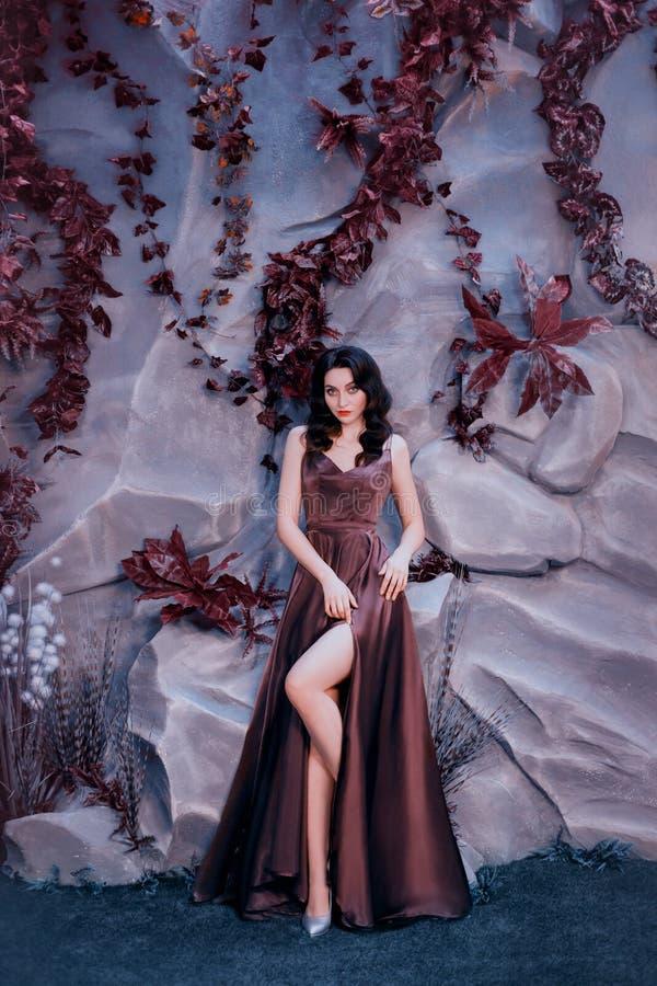 Sexy aantrekkelijke dame met donker gekruld haar tegen steenmuur met ongebruikelijke magische binnen installaties, schitterende c royalty-vrije stock foto