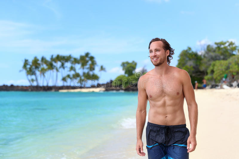 Abs man in swim trunks on beach vacation. Handsome young man looking away on summer beach vacation. Portrait of an attractive caucasian male model with fit body stock images
