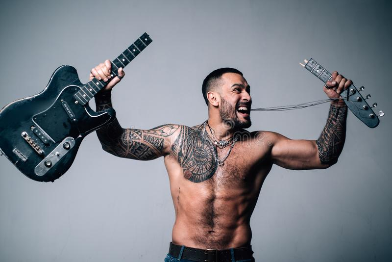 Sexy abs of tattoo man broke guitar. rock concert. confidence charisma. sport fitness, health. brutal sportsman torso. Anger. muscular macho man with athletic stock image